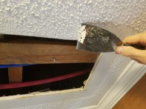 Drywall repair foyer ceiling - Removing texture in preparation for plaster.